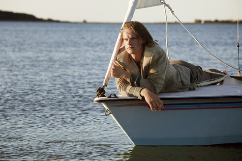 Man looking at view while relaxing on sailboat - CAVF10638