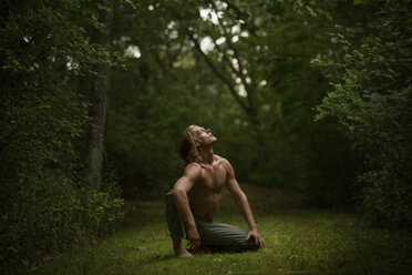 Shirtless man looking up while sitting in forest - CAVF10671
