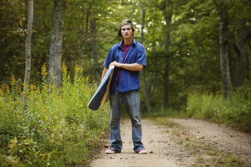 Portrait of man with surfboard standing on dirt road in forest - CAVF10695
