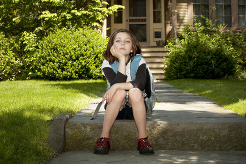 Portrait of girl with backpack sitting on footpath - CAVF10713