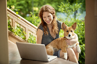 Woman using laptop computer while sitting with dog on porch - CAVF10734
