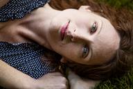 Portrait of woman lying on field - CAVF10737