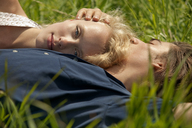 Portrait of woman leaning on man's chest while lying in grass field - CAVF10746