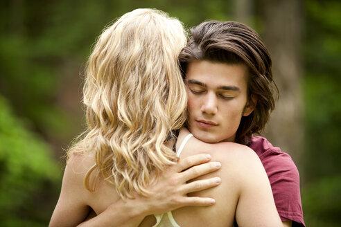 Rear view of woman embracing boyfriend - CAVF10749