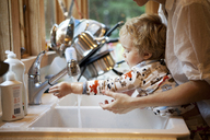 Cropped image of mother assisting son in washing hands at kitchen sink - CAVF10851