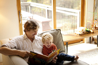 Father reading book with son while sitting on sofa at home - CAVF10893