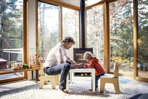 Father teaching son to write while sitting at chair in home - CAVF10896