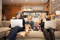 Siblings using mobile phones while sitting with parents on sofa at home - CAVF10932