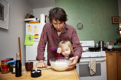 Father assisting son in cooking at home - CAVF10938