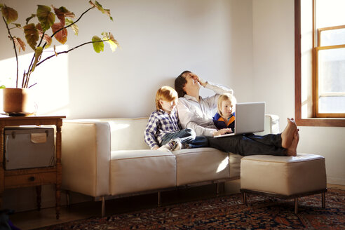 Father using laptop computer while sitting with sons on sofa at home - CAVF10989
