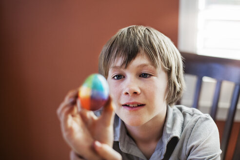 Boy looking at decorated Easter egg while sitting on chair at home - CAVF11142