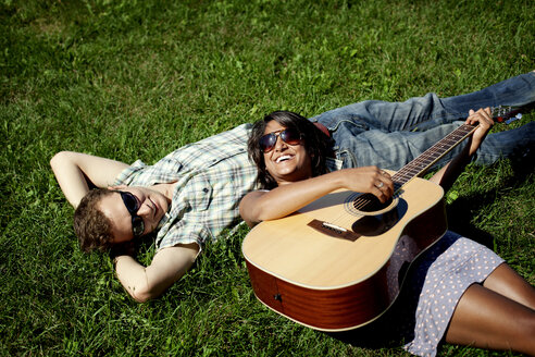 High angle view of couple with guitar lying on grassy field - CAVF11196
