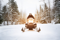 Man riding snowmobile on footpath amidst forest - CAVF11214