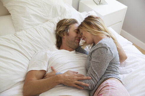 High angle view of couple lying on bed at home - CAVF11226