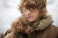 Close-up of man with Poodle dog during winter - CAVF11304