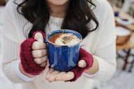 Close-up of woman holding coffee at backyard during winter - CAVF11454