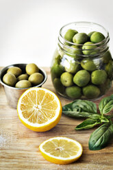 Green olives in containers by sliced lemon on cutting board - CAVF11514