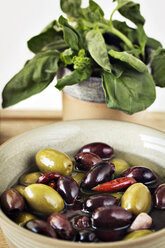 Close-up of olives in bowl by spinach leaves - CAVF11517
