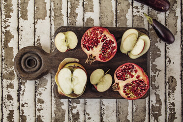 Overhead view of apple and pomegranate on cutting board at table - CAVF11574