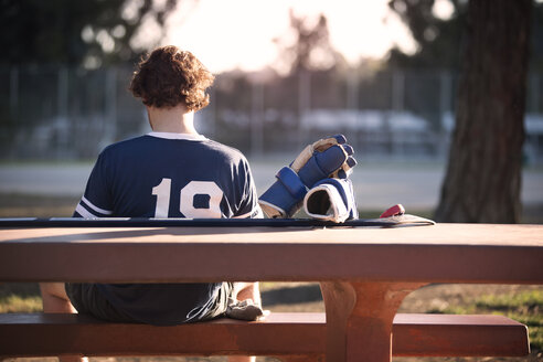 Rear view of roller hockey player sitting on park bench - CAVF11649