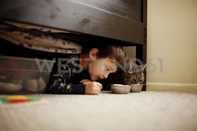 Boy lying by cat under bed at home - CAVF11661