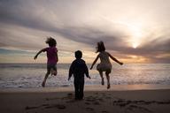 Children enjoying at shore during sunset - CAVF11676