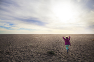 Rear view of girl running on sand against cloudy sky - CAVF11688