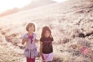 Happy sisters walking on grassy field - CAVF11706