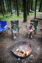 Children roasting marshmallows over fire pit in forest - CAVF11748