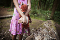 Midsection of girl holding stuffed toy by fallen tree in forest - CAVF11751