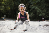 Girl putting sand on legs while sitting on shore at beach - CAVF11757