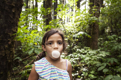 Portrait of girl blowing bubble gum in forest - CAVF11760