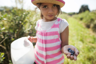 Portrait of girl holding blueberries and container while standing in field - CAVF11775