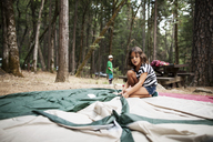 Girl setting up tent in forest - CAVF11778