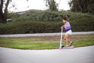 Side view of girl riding push scooter at park - CAVF11850