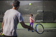 Father and daughter playing tennis on court - CAVF11865
