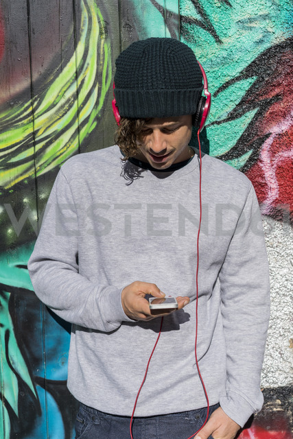 Young man in front of graffity wall hearing music with headphones while using cell phone - AFVF00310