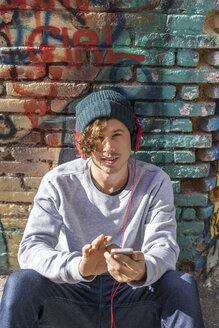Portrait of young man with headphones and cell phone sitting in front of graffiti wall - AFVF00313