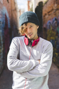 Portrait of young man with headphones wearing wool cap - AFVF00316