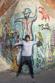 Young man listening music with headphones leaning against graffiti wall - AFVF00325