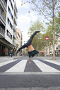 Back view of young man doing handstand on zebra crossing - AFVF00334