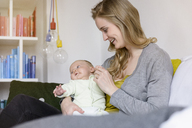 Smiling mother with her baby boy sitting on couch - BMOF00042