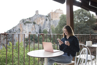 Spain, Alquezar, smiling young woman sitting on terrace with laptop using cell phone - AFVF00335