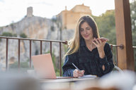 Spain, Alquezar, portrait of smiling young freelancer with laptop and cell phone working on terrace - AFVF00338