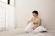 Woman looking away while sitting on bed at home - CAVF11978