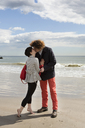 Affectionate couple kissing while standing on shore at beach - CAVF11984