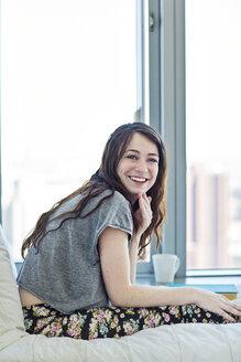 Portrait of smiling woman sitting on bed at home - CAVF12014