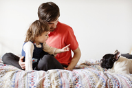 Girl pointing at dog while sitting with father on bed - CAVF12068