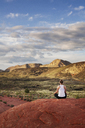Rear view of woman meditating on rock in mountain against sky - CAVF12260