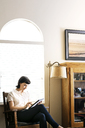 Serious woman using digital tablet while sitting against arch window at home - CAVF12275